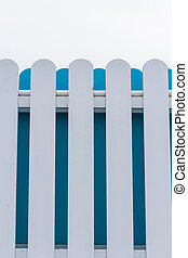 White and blue picket fence with sky