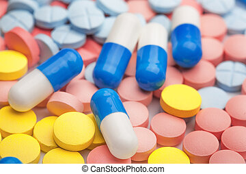 White and blue pills on a background of colored medical ...