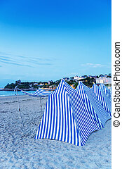 White and blue tents on the beach at sunset