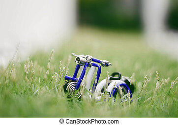 white and blue wired scooter surrounded by green grass. soft and blur. bokeh and retro look