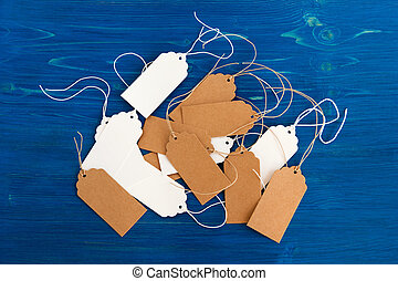 White and brown blank paper price tags or labels set on the blue wooden background, top view.