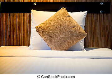 White and brown pillow in white bed