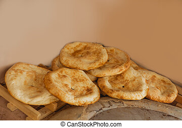 White and brown traditional bread. Round lavashes.