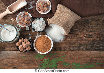 White and cane sugar in different forms on a wooden background.