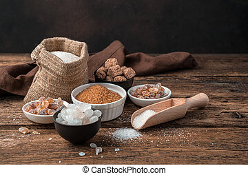 White and cane sugar on a wooden background. Side view with copy space.