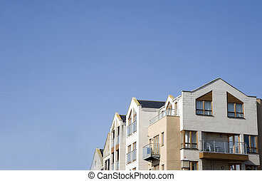 White and cream modern building against deep plain blue sky