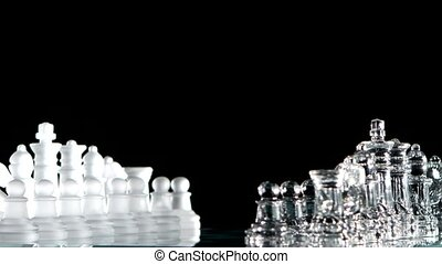White and glass chess is standing on board