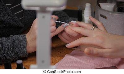 White and gray nail polish woman hands closeup