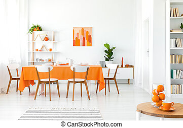 White and orange dining room with painting on the wall, bookshelf in the corner and green plant in the pot