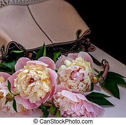 White and pink peonies in a women's pink bag.