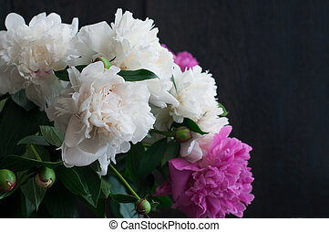 white and pink peonies on rustic wooden background