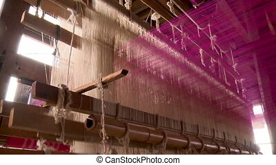 White and pink threads intersecting in the loom