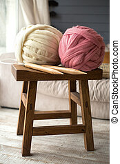 White and pink wool balls with wooden knitting needles on wooden chair in cozy