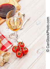 White and red wine, cheese and bread on white wooden table background