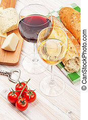 White and red wine glasses, cheese and bread