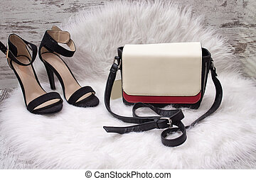 White and red women's bag, black shoes with white fur. Fashionable concept
