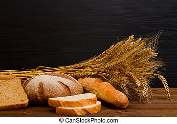 White and rye bread, a loaf, a sheaf on wooden table, black background, space for text