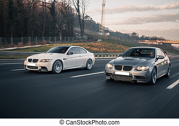 White and silver cars passing each other on the highway