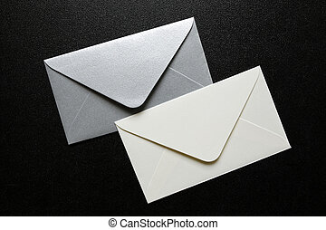 white and silver envelopes on black background