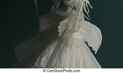 white angel on a swing comes down