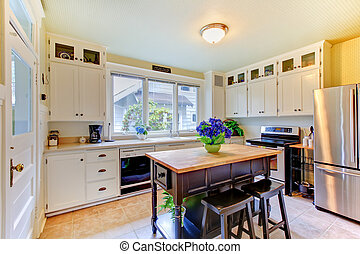 White antique remodeled kitchen with black island. -...