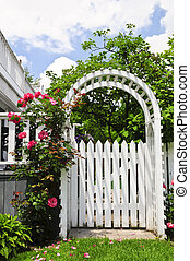 White arbor in a garden - White arbor with red blooming...