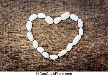 white arrangement of stones forming a heart shape on background