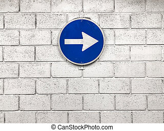 white arrow on blue road sign hanging on wall pointing right direction -