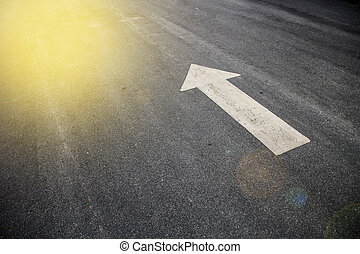 Drawing a frayed white arrow on the asphalt with sunlight
