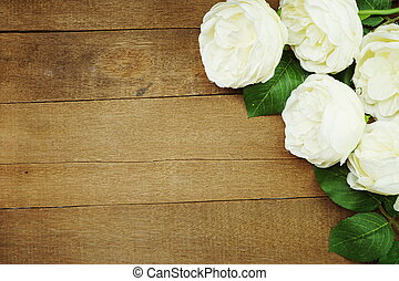 White artificial flower border frame with space copy on wooden background