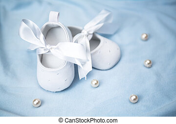 White baby booties on blue blanket with pearls