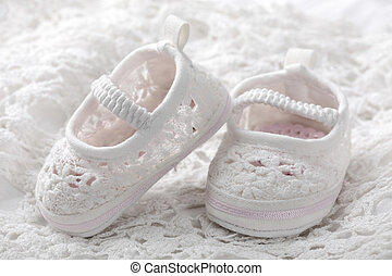 White baby booties on white background