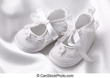 White baby booties on white silk