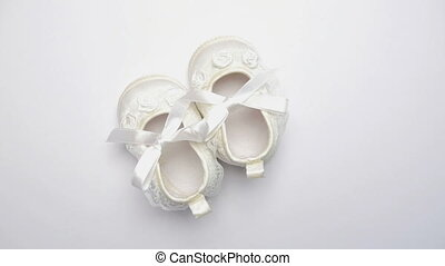 White baby booties on revolving white surface