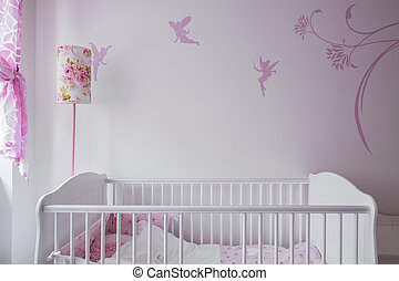 White baby cot - Image of white baby cot with wall decor in...