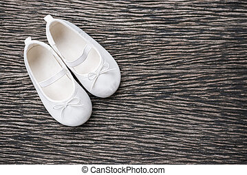 White baby shoe on wooden background , top view