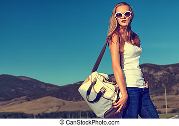 white bag - Beautiful young woman posing on a road over ...
