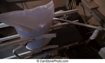 White bag of wheat grain moves along conveyor vertically and falls on horizontal conveyor belt, close-up