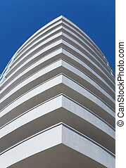 white balconies of a modern residential building on a clear blue sky