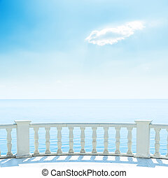 white balcony near sea and blue sky with clouds