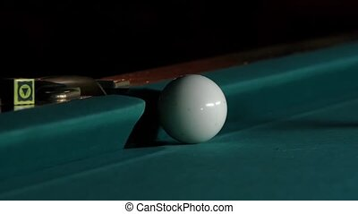 White ball falls into a pocket billiard after impact. Close up. Slow motion