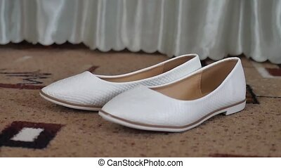 white ballet flat shoes with beige bag, standing stand on...