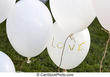 White balloons over grass saying 'Love' at a wedding reception