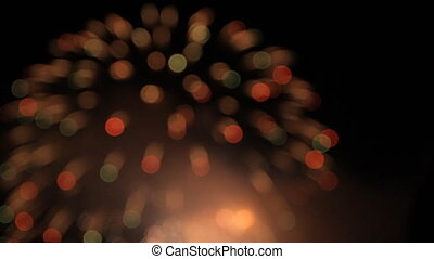 White balls of fireworks changing into red and green as they open. Bokeh.