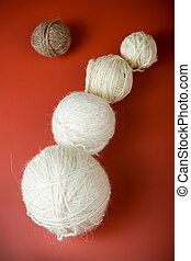 white balls of yarn of various sizes on a red background