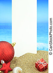 White banner and Christmas ornaments on the beach