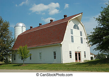 The afternoon sun shines warmly on the front of an old white barn in the country in Kentucky, USA.