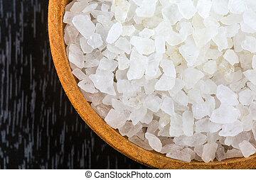 White bath salt in a wooden bowl closeup.