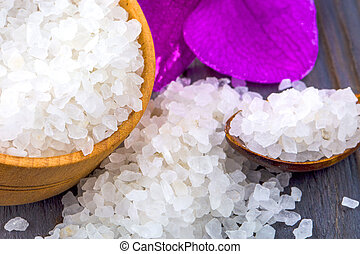 White bath salt in a wooden bowl with a spoon and an orchid