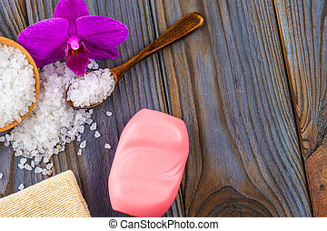 White bath salt in a wooden bowl with a spoon, soap, burlap and orchid